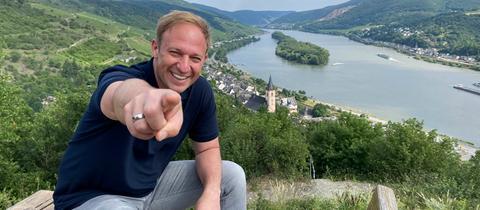 """Tobias Kämmerer an der """"schönsten Weinsicht"""" in Lorch. Er lächelt und zeigt in die Kamera."""