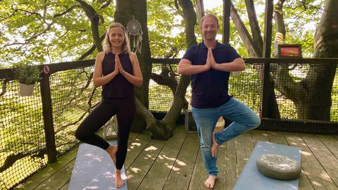 Tobias Kämmerer beim Baumkronen Yoga auf dem Hoherodskopf mit Laura Herburg.