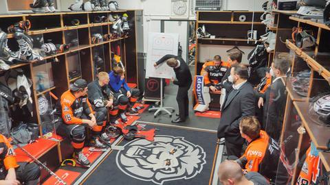 Die Umkleidekabine der Löwen Frankfurt. Die Spieler sitzen auf Bänken, der Trainer steht an einer Tafel und zeichnet Spielzüge ein.