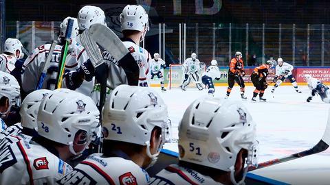 Die Spieler der Kassel Huskies sitzen auf der Bank, im Hintergrund ist das Spielfeld zu sehen.