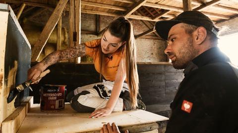 Lisa Manns streicht eine Holzwand, Joschi Waldeck schaut ihr dabei zu.