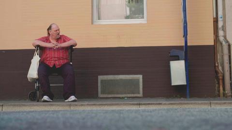 Ein Rentner wartet an der Bushaltestelle