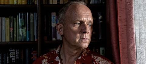 Ulrich Tukur mit finsterem Blick im roten Hawaii Hemd