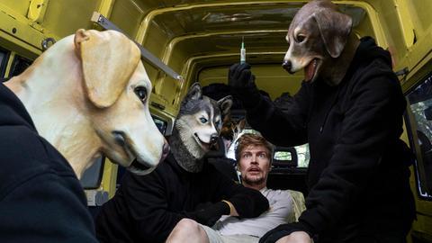 Frederick Seibold wird von einer Gruppe maskierter Personen festgehalten. Die Personen tragen Hundemasken und einer will Frederick mit einer Spritze betäuben.
