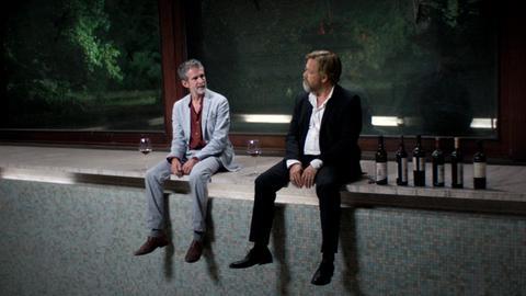 Malte Klingsor (Ulrich Matthes, li.) und Patrick Laubenstein (Justus von Dohnányi) sitzen am Poolrand mit einigen Flaschen Rotwein