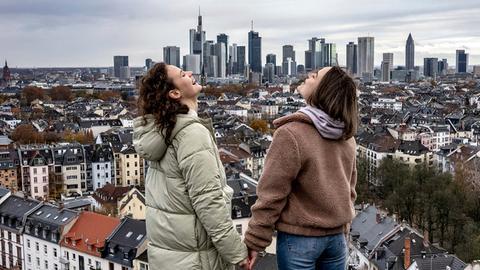"""Luise """"Luna"""" Nathan (Jana McKinnon) und Nellie """"Luna"""" Kunze (Lena Urzendowsky, rechts im Bild.) stehen auf einem Dach und schauen auf die Frankfurter Skyline."""