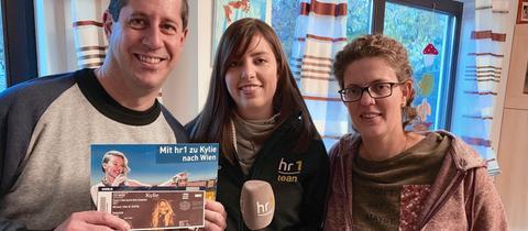 hr1-Reporterin Kim Horbach (Mitte) überrascht Jens und Dorothee Holste aus Ginsheim-Gustavsburg, die eine Reise zum Konzert von Kylie Minogue in Wien gewonnen haben
