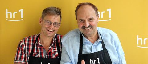 """Spitzenkoch Johann Lafer (r) und Moderator Uwe Berndt (l) tragen Schürzen mit der Aufschrift """"hr1-Chefkoch"""" und lächeln in die Kamera"""