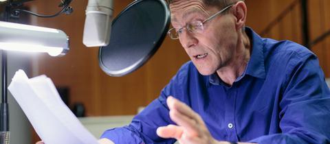 """Udo Schenk sitzt im hr-Hörspielstudio vor dem Mikro und spricht seine Rolle als """"Stadler"""" in """"Evangelium Pasolini"""" ein"""