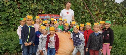 """Kindergarten """"Weschnitz-Wichtel"""" aus Einhausen mit ihrem Gewinnerkürbis """"Fanti 2"""" und hr3-Moderator Christian Kaempfert."""