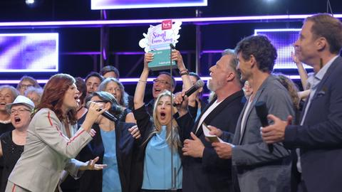 """Die Mitglieder von """"Borussia Sängergruß"""" jubeln als Sieger auf der Bühne des hr4-Chorwettbewerbs 2019"""