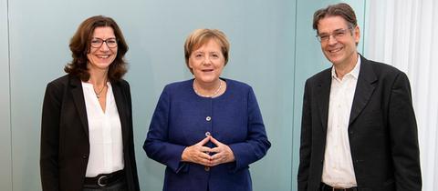 Kanzlerin Angela Merkel (m.) mit hr-iNFO-Programmchefin Katja Marx und Hauptstadtkorrespondent Andreas Reuter