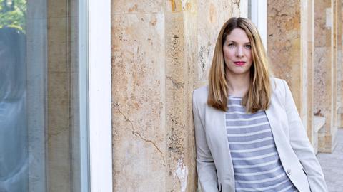 Katharina Wilhelm lehnt an der Wand eines Gebäudes (Hessischer Rundfunk)