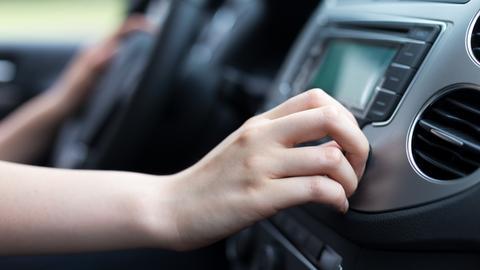 Person sucht Sendeprogramm im Auto
