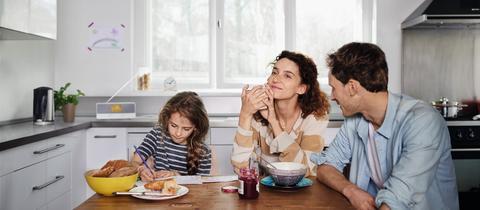 Eine Familie sitzt in der Küche und hört Radio