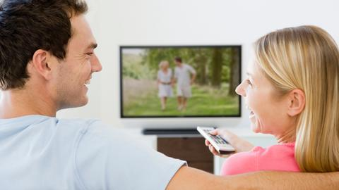 Junges Paar sitzt vor einem Fernsehgerät, die Frau hält eine Fernbedienung in der Hand.