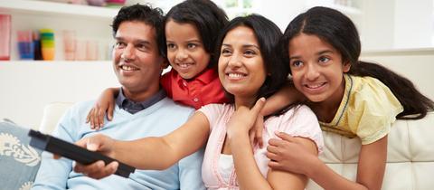 Eine Familie sitzt mit einer Fernbedienung auf dem Sofa und schaut Fernsehen