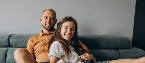 Paar sitzt auf dem Sofa und schaut fern