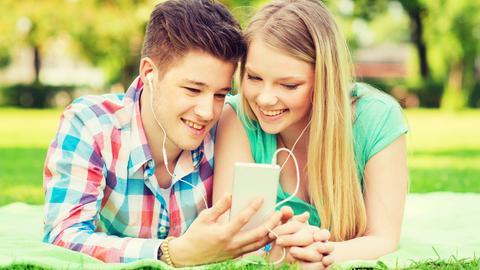 Teenager auf einer Wiese hören Radio über das Handy