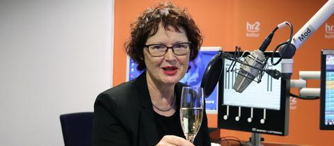Angelika Bierbaum mit Sektglas im hr2-Studio.