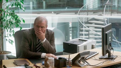 """Verzweifelt und entsetzt am Schreibtisch: Joachim Król im ARD-Dokudrama """"Gier frisst Herz"""""""