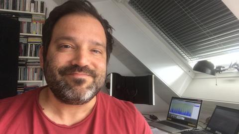 Alexander Göbel sitzt an seinem Schreibtisch im Homeoffice und lächelt in die Kamera.