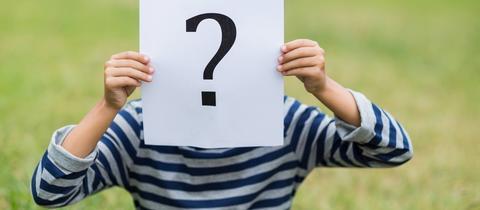 Jugendlicher hält sich ein Blatt mit einem aufgedruckten Fragezeichen vor das Gesicht