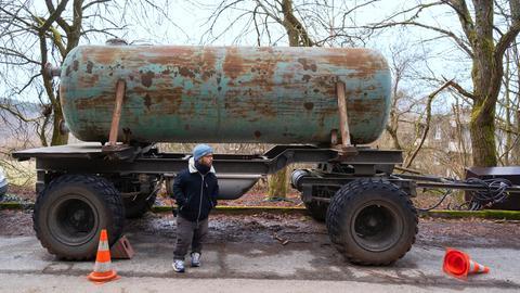 Tankwagen (Anhänger) eines Landwirts steht auf einer Straße, davor steht Motivaufnahmeleiter und Green Consultant Robert Hertel