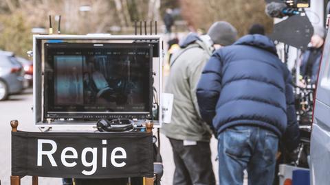 Regiestuhl und Monitor draußen am Set, daneben stehen in Rückansicht zwei Männer