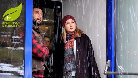 Familie (Vater, Mutter, dahinter Kind) schauen aus dem Eingangsbereich einer Tür hinaus in den dichten Graupelregen. Filmszene mit Serkan Kaya, Katja Studt
