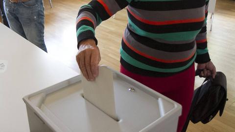 Wählerin wirft Umschlag in eine Wahlurne
