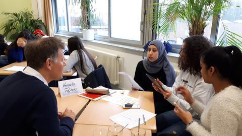 Sebastian Kisters spricht in einem Klassenzimmer mit Schülerinnen.