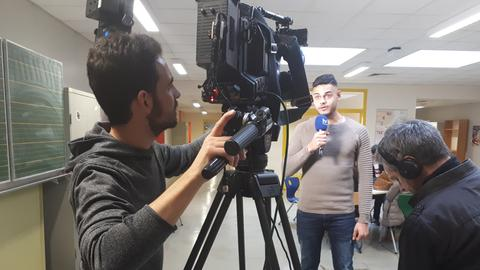 Ein Schüler filmt mit einer Kamera einen anderen Schüler, der in ein Mikrofon spricht.