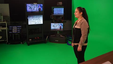 Eine Schülerin steht im Studio vor dem Green-Screen und Vorschau-Monitoren.