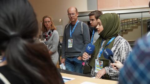 Eine Schülerin mit Kopftuch hält, umgeben von Schülern und Lehrern, ein Mikrofon in der Hand.