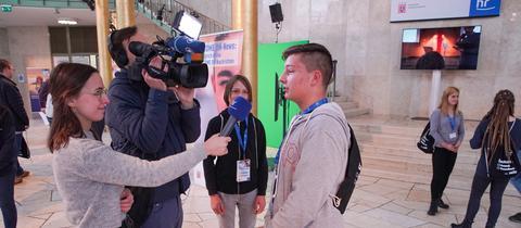 In der Goldhalle des Hessischen Rundfunks interviewt eine Schüler-Reportertin einen teilnehmenden Schüler vor der Kamera.