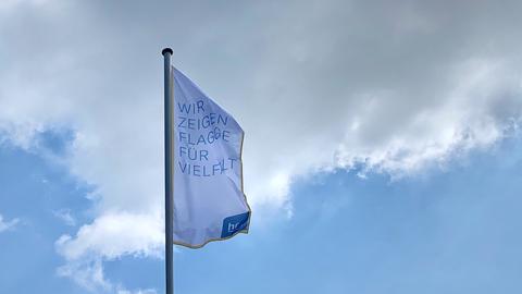 """Fahne mit der Aufschrift """"Wir zeigen Flagge für Vielfalt"""" vor dem Haupteingang des hr."""