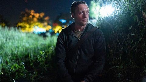 Stephan Ernst (dargestellt von Robin Sondermann) steht nachts am Feldrand und beobachtet die Terrasse von Walter Lübcke aus der Ferne.