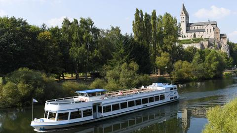Lahn mit Ausflugsschiff, im Hintergrund die Lubentius-Basilika im Stadtteil Dietkirchen.