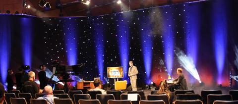 """Kabarettist Florian Schroeder vor leeren Stuhlreihen auf der Bühne im hr-Sendesaal , Aufzeichnung """"Florian Schroeder-Satireshow"""""""