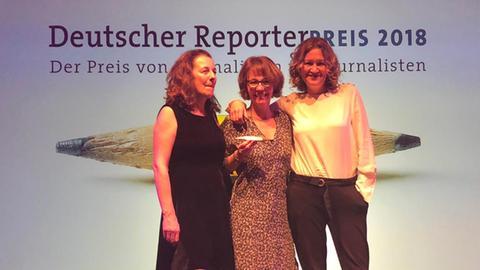 Christine Rütten, Petra Boberg und Christina Sianides stehen auf einer Bühne