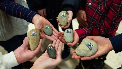 In den Händen der Gewinner liegen kreisförmig die Onkel-Otto-Steine