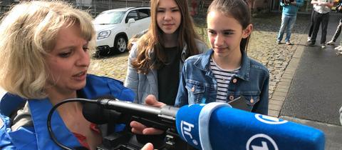 hr-Mitarbeiterin Sabrina Kurth zeigt zwei Mädchen, wie eine Kamera funktioniert.