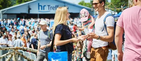 Eine hr-Mitarbeiterin verteilt Flyer vor dem hr-Treff