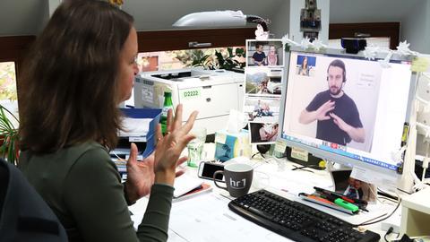 Eine gehörlose Frau gebärdet vor einem PC-Monitor - sie telefoniert. Auf dem Monitor ist ein Gebärdensprachdolmetscher zu sehen sowie die hörende Anruferin.