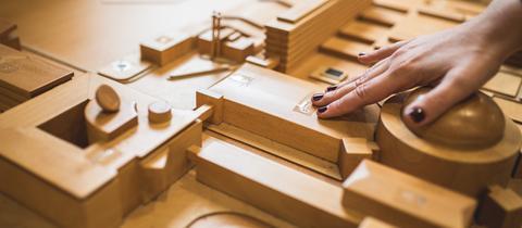 Ein aus Holz gefertigter taktiler Lageplan mit den Gebäuden des hr, dazu Beschriftung in Braille. In Großaufnmahme eine Hand, die fühlt.