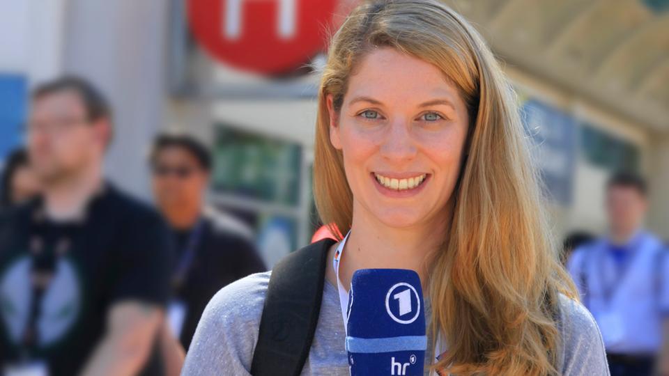 Katharina Wilhelm hält ein Mikrofon in der Hand und steht auf der Straße