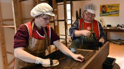 Zwei Frauen in der Kautabakmanufaktur vor plattgewalzten Tabakblättern