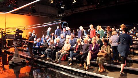 Zahlreiche Komparsen sitzen als Publikum im Fernsehstudio.