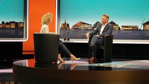 Im Fernsehstudio führt der fiktive Moderator ein Interview mit einem fiktiven weiblichen Talkgast.